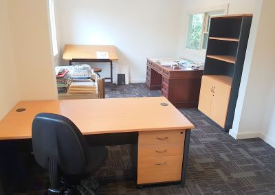 Office desk, mobile pedestal and office chair. In the background half door cupboard and bookshelf